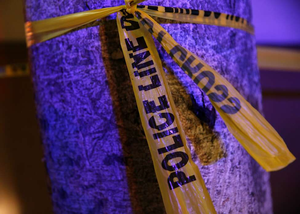 Police tape glows in the blue light from police cruiser at the site of a shooting outside the parking garage at Fifth and Mission streets in San Francisco, California, on Wednesday, Nov. 25, 2015.