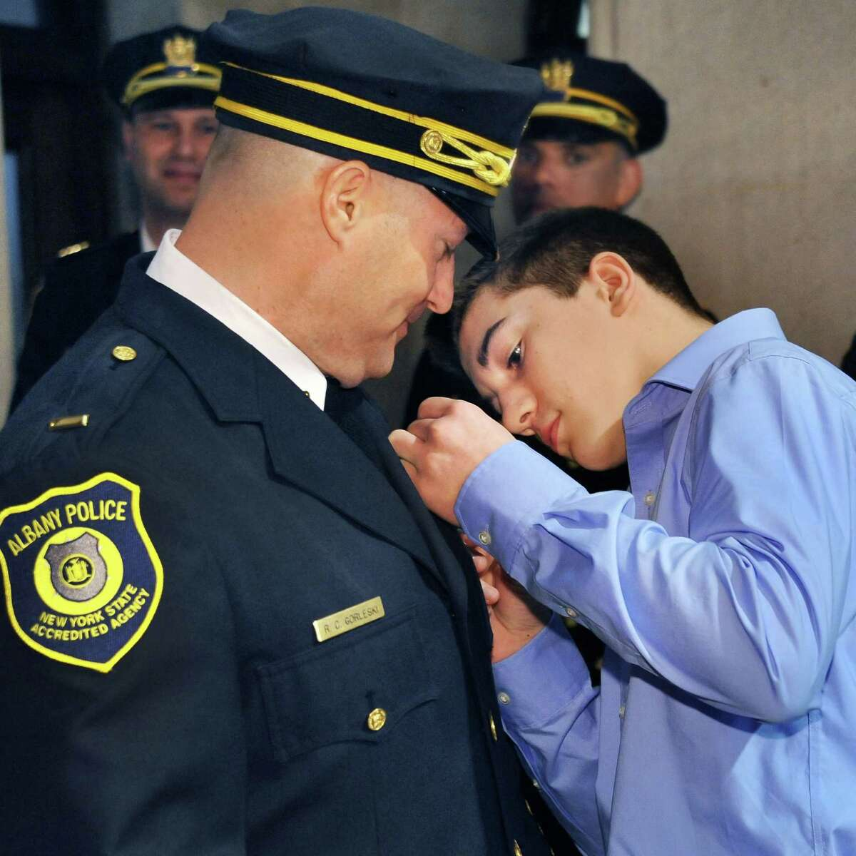 Newly promoted Albany Police Lieutenant Richard Gorleski has his badge pinned on by son Cole Gorleski, 15, during a ceremony in the City Hall Rotunda on Friday morning, March 11, 2016, in Albany, N.Y. (John Carl D'Annibale / Times Union)
