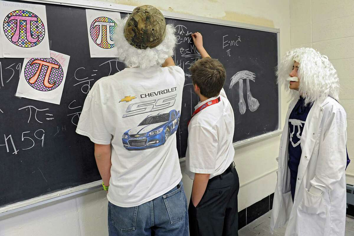 From left, students Cameron Canfield, 15, and Michael Sullivan, 12, write variations of pi on the chalk board as eighth-grade algebra teacher Mike Dempsey watches at Catholic Central High School Friday, March 11, 2016 in Troy, N.Y. The students and teacher were dressed up like Albert Einstein for the Pi Day celebration. (Lori Van Buren / Times Union)