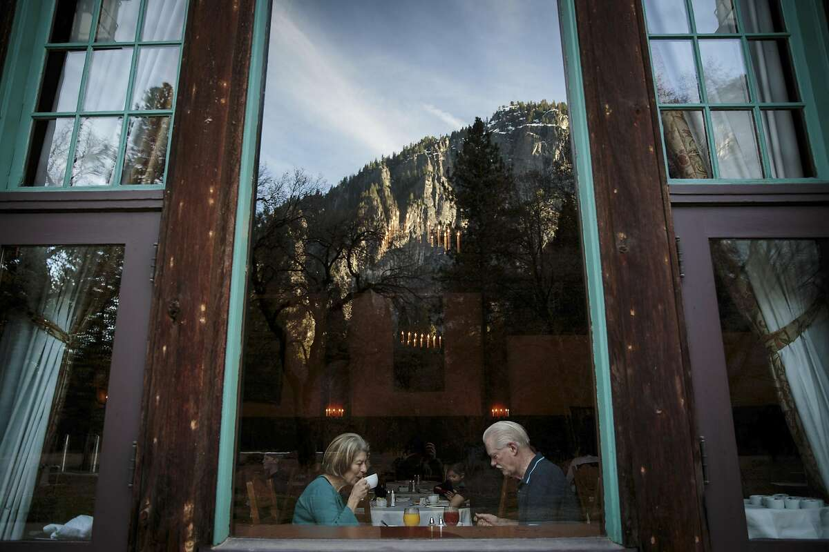 Carol and Richard Anderson eat breakfast in the dining hall of what was once The Ahwahnee hotel -- recently renamed The Majestic Yosemite Hotel -- at Yosemite National Park in California, March 1, 2016. Delaware North, a company that until recently ran the park�s hotels, restaurants and shops, has caused an uproar by having apparently successfully trademarked several names associated with the national park, including the name of the park itself. (Max Whittaker/The New York Times)