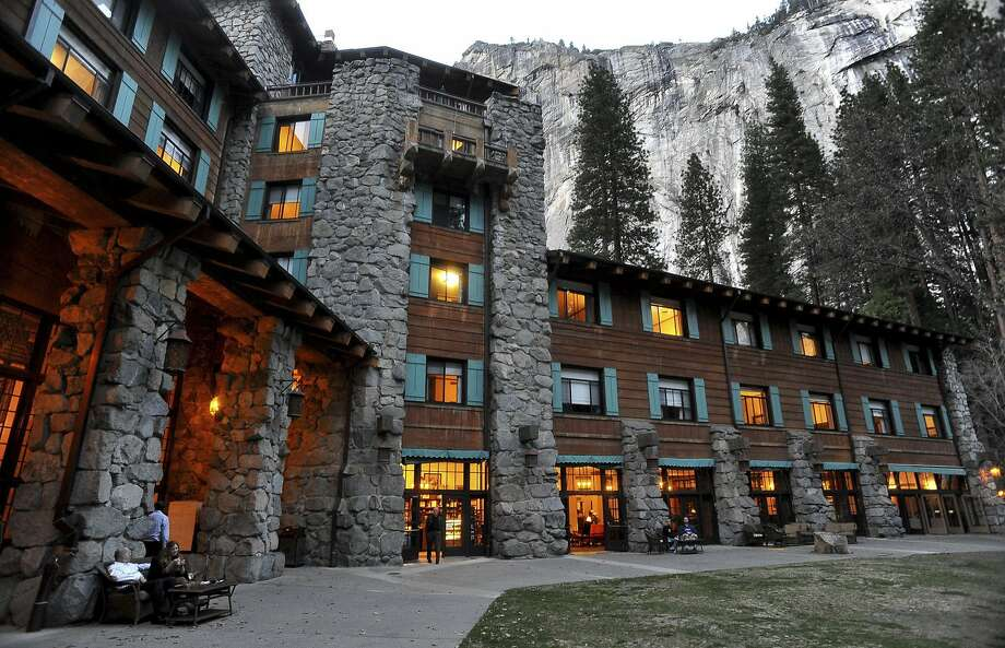 In this March 24, 2014 file photo, the historic Ahwahnee Hotel is lit up as dusk falls over Yosemite National Park, Calif. A new concessionaire takes over Tuesday at the park and many of the landmark places will have name changes at least temporarily because the old concessionaire lays claim to the names. The famed Ahwahnee Hotel is set to become the Majestic Yosemite Hotel.  Photo: John Walker, AP