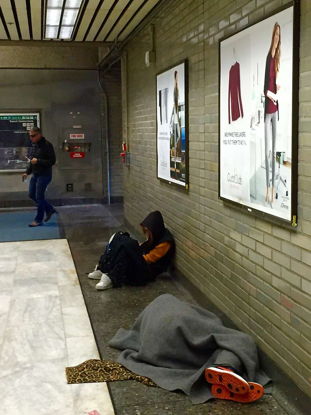 Homeless take refuge inside the Civic Center BART station. The transit agency is taking new steps to clean up its stations, including keeping homeless out overnight.