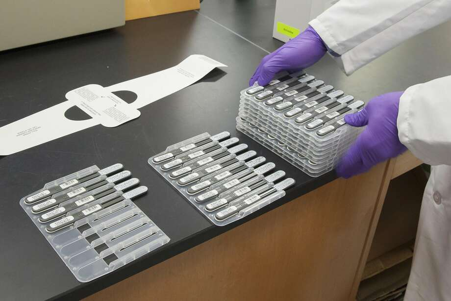 A criminalist with the State of California Department of Justice Bureau of Forensic Services stacks offenders' DNA collectors at the State DNA Laboratory in Richmond. Photo: Peter DaSilva, Special To The Chronicle