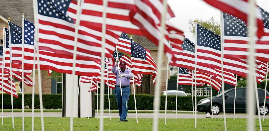 Lawrence Holly, a member of the Exchange Club of Killeen, adjusts one of the 490 American flags placed around the Fort Hood November 5 Memorial Thursday March 10, 2016 at the Killeen Civic and Conference Center in Killeen, Tx. The memorial to the 13 people killed and 31 wounded Nov. 5, 2009 by gunman Army psychiatrist Nidal Hasan will be dedicated Friday March 11, 2016. Texas Gov. Greg Abbott will present Texas Purple Heart medals to family members of the deceased and to the wounded survivors. Photo: Edward A. Ornelas, Staff / San Antonio Express-News / © 2016 San Antonio Express-News