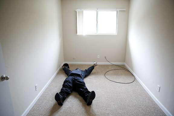 "After sleeping in his car for almost a year, Randy ""P Money"" Harrison lays on his bedroom floor and celebrates after moving into an apartment in Benicia, Calif., on Friday, March 11, 2016."