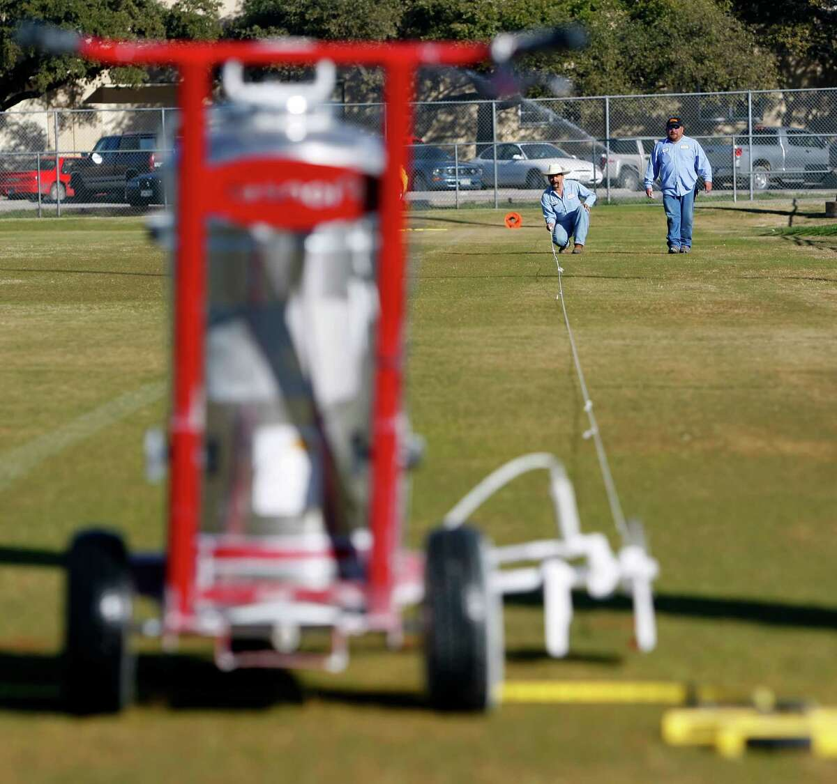 A San Antonio Independent School District employee prepares to stripe a field at the district's sports complex. In the long run, a higher minimum wage would hurt district workers.