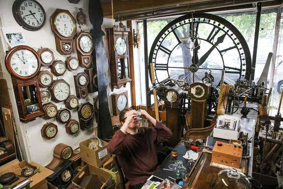 Clock-maker's apprentice Maxwell Nesbet, fixes a pocket watch at his desk at Dorian Clair's clock repair shop in Noe Valley, San Francisco, California, on Friday, March 11, 2016. Maxwell may be helping Dorian Clair reset the time on the Ferry Building clock this year for daylight savings.