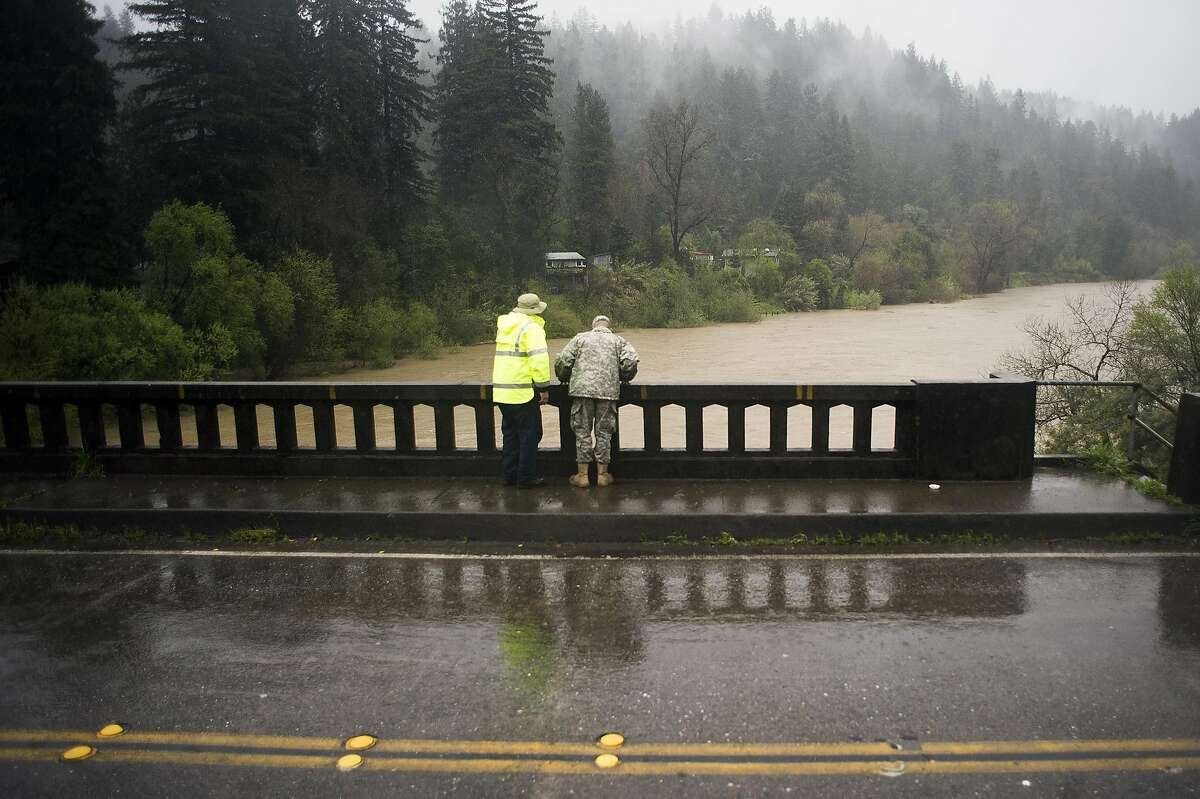 Two pedestrians watch low level flooding on the Russian River in Guerneville, CA on March 11, 2016.