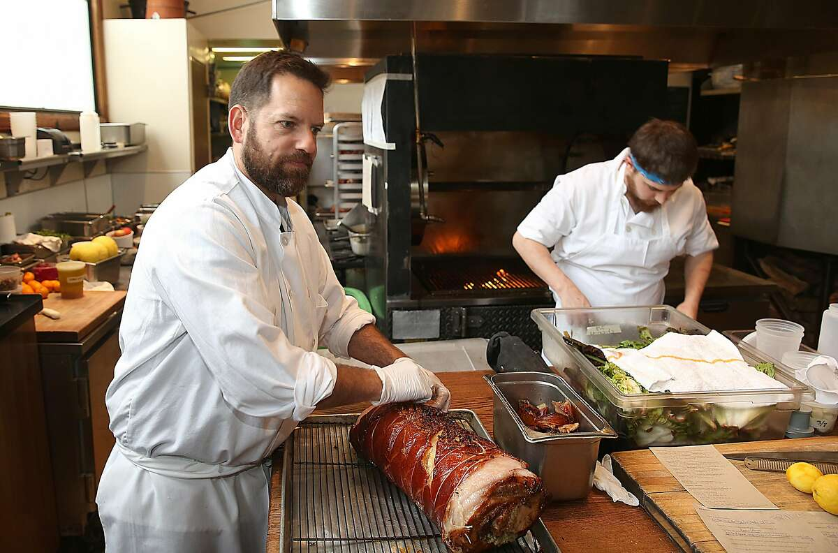 Owner/chef Laurence Jossel pulls pork at his restaurant in San Francisco, California, on tuesday, march 8, 2016. At right is grill cook Austin Thompson. Nopa is celebrating it's tenth anniversary.