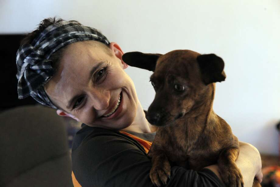 Season of Sharing recipient Shandi Anderson holds Little Mama, a neighbor's dog, in the public housing apartment she shares with her mother, Karen Fabec in Marin City, Calif., on Wednesday, December 23, 2015. Photo: Carlos Avila Gonzalez, The Chronicle