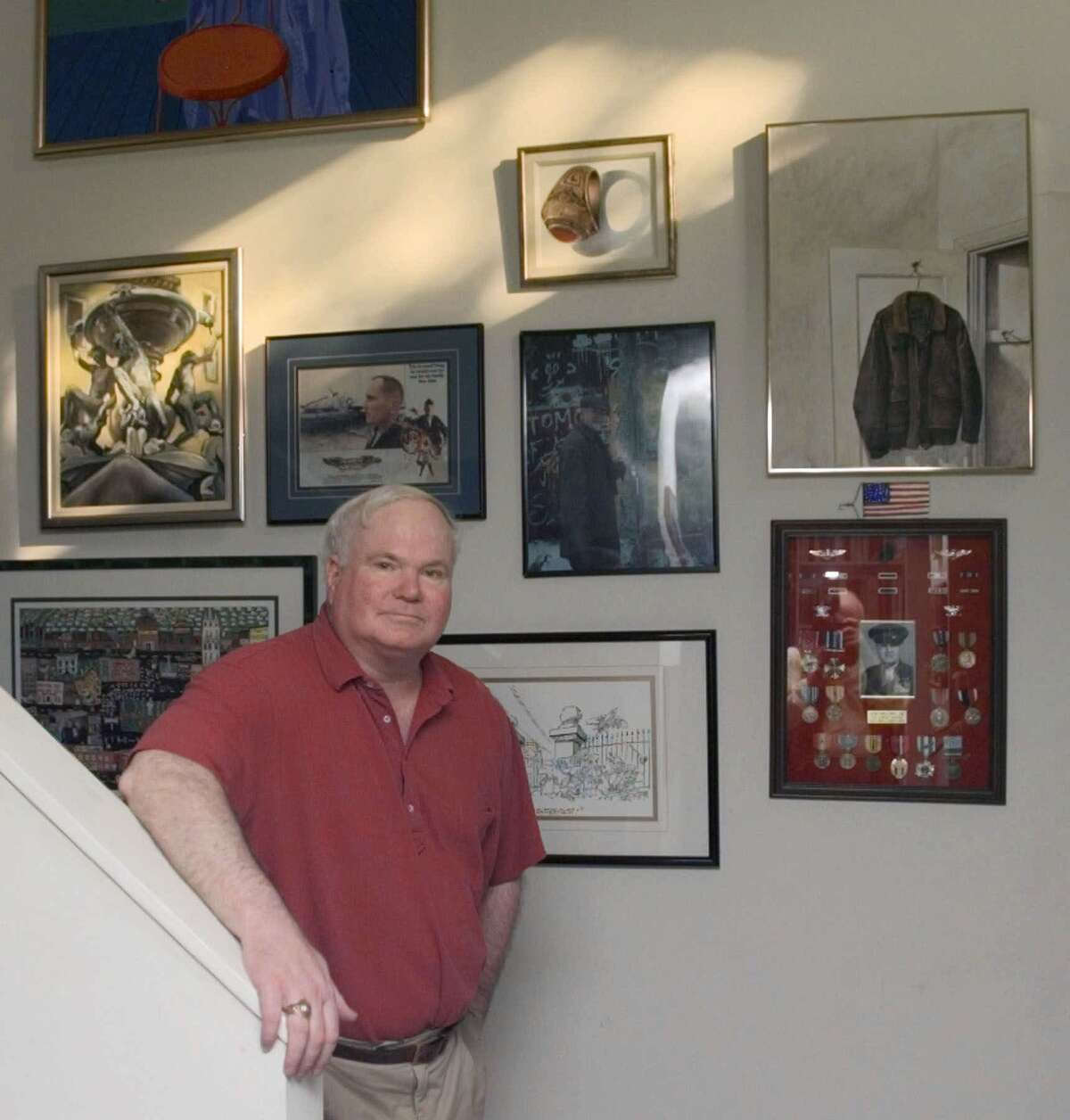 """Novelist Pat Conroy poses by posters and momentos of his late father, a Marine colonel and the subject of Conroy's autobiographical novel """"The Great Santini,"""" in his home on Fripp Island, S.C. on Nov. 3, 2000."""