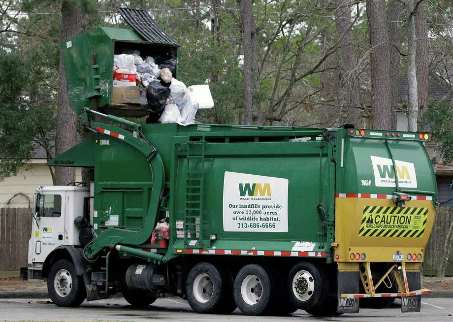 A dumpster is emptied by a Waste Management truck in Houston. (AP Photo/David J. Phillip) Photo: David J. Phillip, STF / AP
