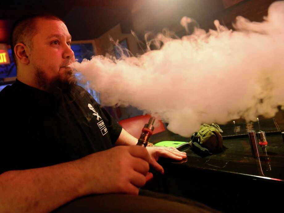 Bruce Belisle vapes at The Mod House Vapor Emporium on River Street in Milford, Conn. The Ansonia Board of Aldermen decidede not to include vaping in a ban prohibiting smoking and chewing tobacco products in the city's parks, recreational sites and athletic fields. Photo: Christian Abraham / Hearst Connecticut Media / Connecticut Post