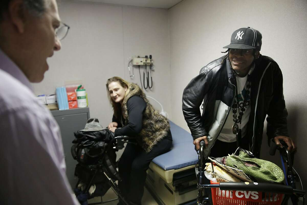 Dr. Barry Zevin (l to r), Homeless Outreach Team medical director, talks with Pier 80 shelter clients Melinda Welsh and Timothy Blevins at the Pier 80 medical clinic on Wednesday, March 9, 2016 in San Francisco, California.