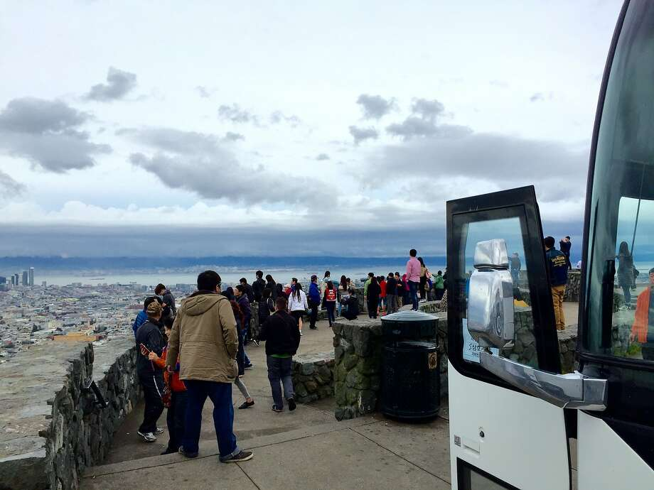 A bus load of foreign tourists enjoy the view from Christmas Tree Point on the southeast edge of Twin Peaks. Parking in the area could get more difficult� may get m Photo: Andrew Ross, San Francisco Chronicle