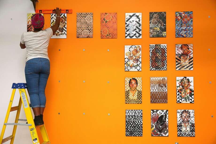 "Artist Tosha Stimage installs her artwork called ""50 Ways to Make Orange,"" a woven collage, at 1275 Minnesota Street. Photo: Liz Hafalia, The Chronicle"