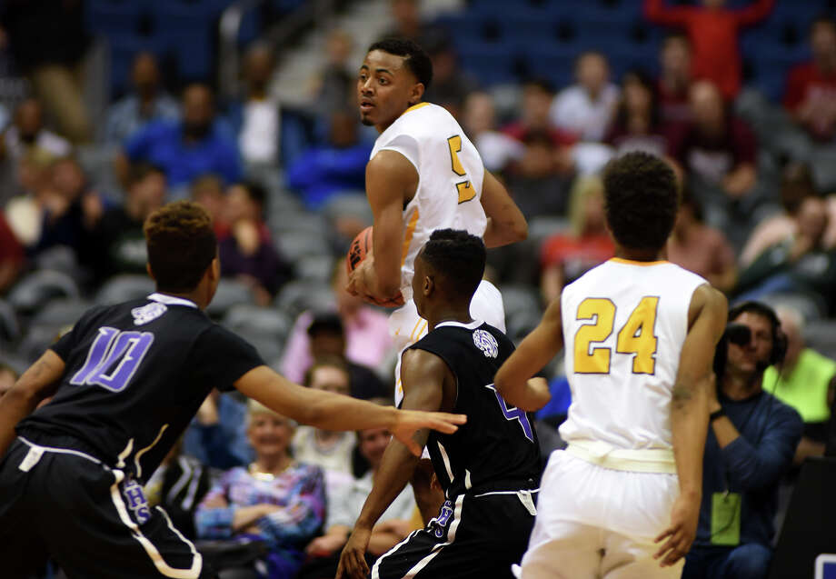 La Marque senior guard Tavier Blaine, top, works a rebound against a pair of  Dallas Lincoln defenders during the 4th quarter of their Class 4A boys basketball state semifinal matchup at the Alamodome in San Antonio on Friday, Mar. 11, 2016. (Photo by Jerry Baker/Freelance) Photo: Jerry Baker, For The Houston Chronicle