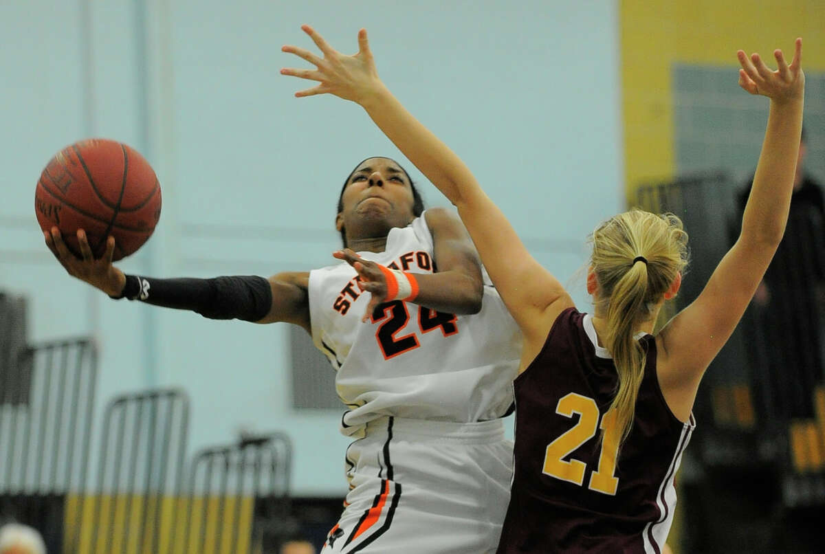 Stamford Tiana England puts up a shot under pressure from South Windsor Keegan Caffrey in a CIAC 2016 State Girls Basketball Tournament Class LL semifinal game at John F. Kennedy High School in Waterbury, Conn on March 11, 2016. Stamford defeated South Windsor 66-57.