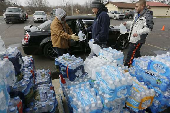 Volunteers load a vehicle with bottled water at Our Lady of Guadalupe Church, Friday, Feb. 5, 2016 in Flint, Mich. Michigan Gov. Rick Snyder is defending how his office responded to an email flagging a potential link between a surge in Legionnaires' disease and Flint's water. (AP Photo/Carlos Osorio)