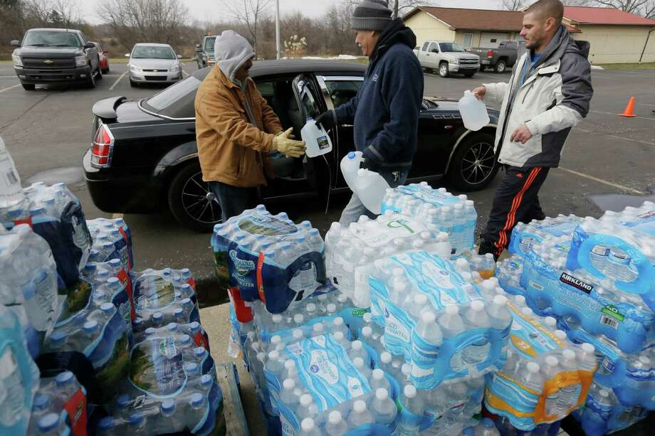 Volunteers load a vehicle with bottled water at Our Lady of Guadalupe Church, Friday, Feb. 5, 2016 in Flint, Mich. Michigan Gov. Rick Snyder is defending how his office responded to an email flagging a potential link between a surge in Legionnaires' disease and Flint's water. (AP Photo/Carlos Osorio) Photo: Carlos Osorio, STF / Associated Press / AP