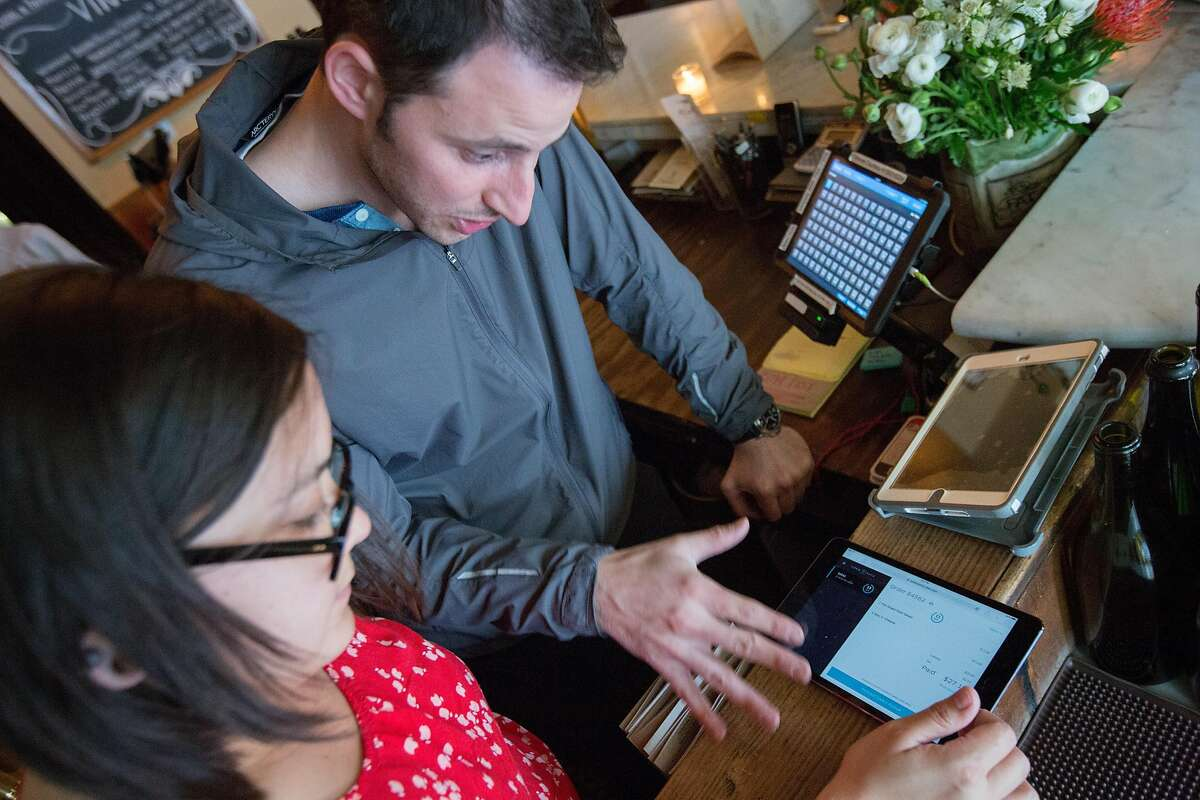 From left: Fat Angel manager Laura Tsim and Hi Neighbor group partner Ryan Cole check on an UberEATS order on Friday, March 11, 2016, in San Francisco, Calif. Starting Tuesday, Uber is expanding its delivery service from limited items to full menu offerings from more than 100 restaurants.