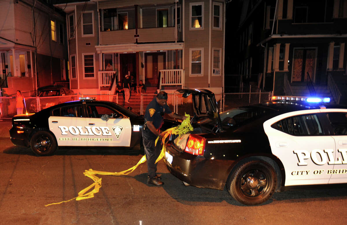 A Bridgeport police officer puts away police tape after two pedestrians were struck by a vehicle on Fairfield Avenue near the intersection of Clinton Avenue in Bridgeport, Conn. on Wednesday September 4, 2013.