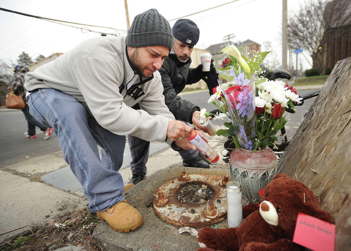 Neighborhood residents Sammy Negron, left, and Victor Nazario light candles on a small memorial to Carmen Martinez, who was struck and killed by a pickup truck while crossing John Street, near the location of the accident in Bridgeport, Conn. on Tuesday, January 12, 2016.