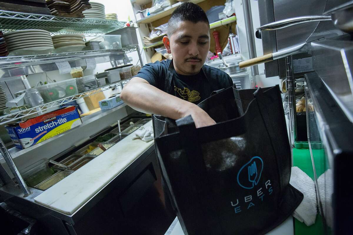 Fat Angel cook Eduardo Bojorquez bags a fresh meal that was ordered through UberEATS on Friday, March 11, 2016 in San Francisco, Calif. Starting Tuesday, Uber is expanding its delivery service from limited items to full menu offerings from more than 100 restaurants.