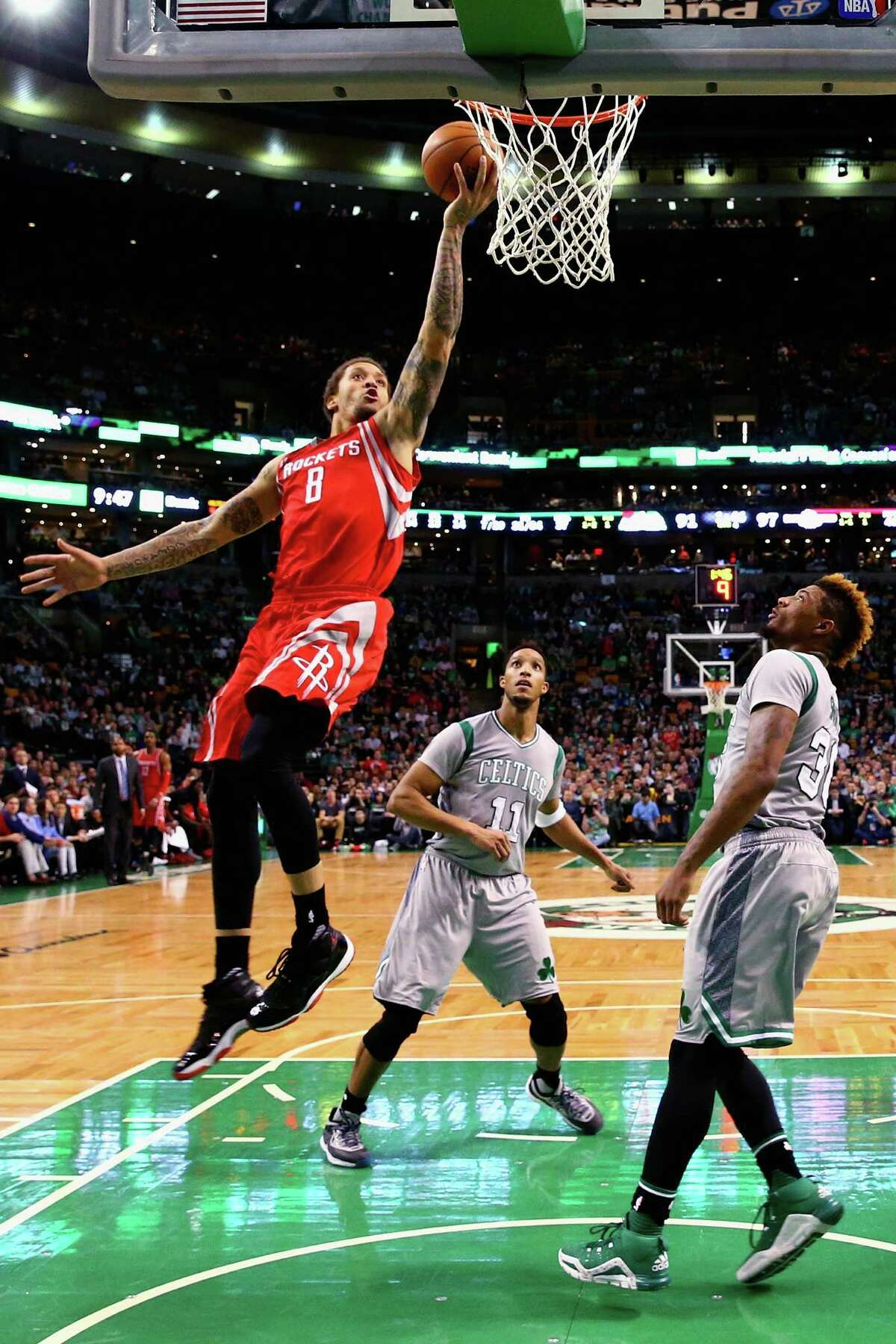 BOSTON, MA - MARCH 11: Michael Beasley #8 of the Houston Rockets takes a shot over Marcus Smart #36 and Evan Turner #11 of the Boston Celtics during the second half at TD Garden on March 11, 2016 in Boston, Massachusetts. The Rockets defeat the Celtics 102-98. NOTE TO USER: User expressly acknowledges and agrees that, by downloading and/or using this photograph, user is consenting to the terms and conditions of the Getty Images License Agreement.