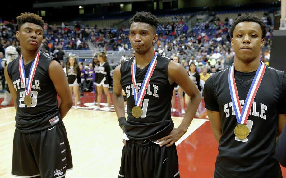Steele senior Kijana Love (center) shows his disappointment after getting a state semifinal medal with teammates Trivero Wilson (23) and Sterling Parker after the Knights lost to DeSoto in overtime the 6A boys basketball tournament at the Alamodome on March 11, 2016. Photo: Tom Reel /San Antonio Express-News / 2016 SAN ANTONIO EXPRESS-NEWS