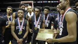 The Steele Knights gather around their state semifinal trophy after losing to DeSoto in the state 6A boys basketball tournament at the Alamodome on March 11, 2016.