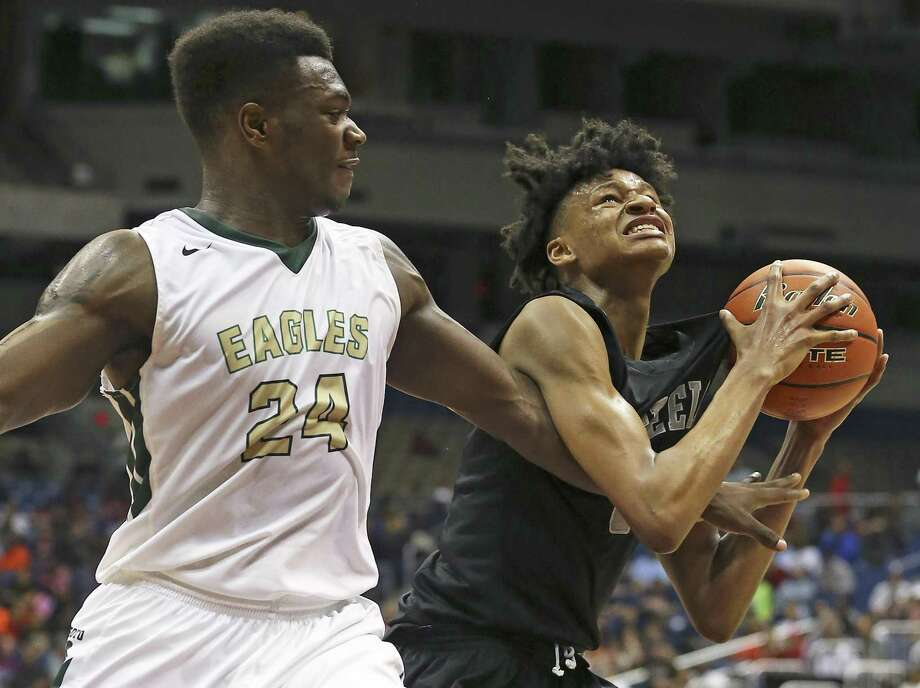Steele forward Gerald Liddell struggles underneath the hoop for a shot against DeSoto's Tristen Wallace in the state 6A boys basketball semifinals at the Alamodome on March 11, 2016. Photo: Tom Reel /San Antonio Express-News / 2016 SAN ANTONIO EXPRESS-NEWS