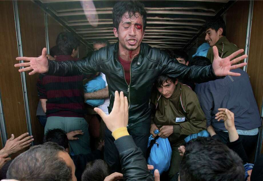 An injured man pleads with crowds of migrants scuffling to grab aid from a truck at the northern Greek border station of Idomeni, Friday, March 11, 2016. After nearly three days of rain, conditions in the refugee camp on the Greek-Macedonian where about 14,000 people are stranded have deteriorated significantly, with many of its residents struggling to re-pitch their small camping tents in slightly drier patches.(AP Photo/Vadim Ghirda) ORG XMIT: XVG116 Photo: Vadim Ghirda / AP