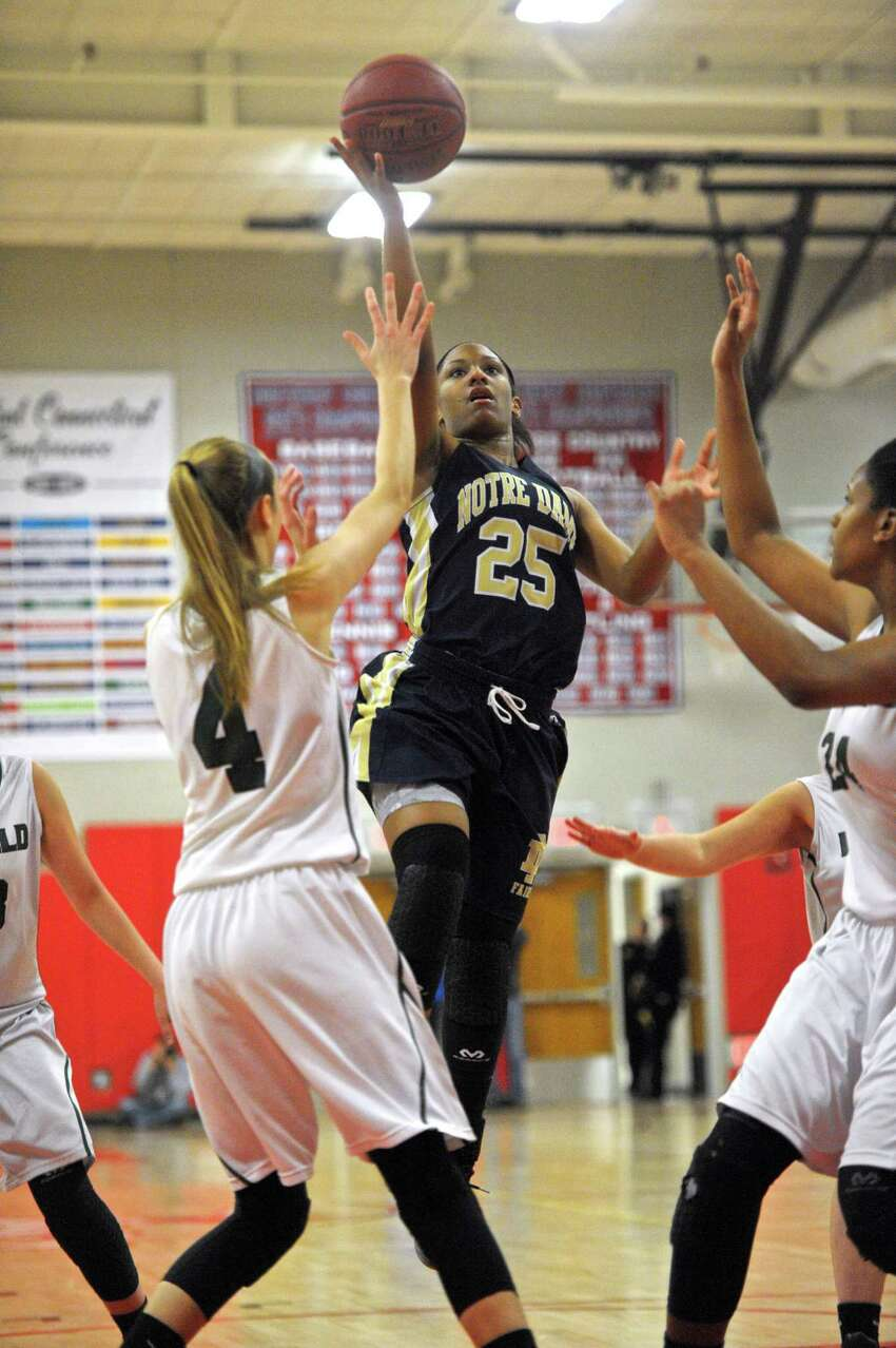 Notre Dame-Fairfield's Dayniera Artis (25) drives to the basket between Enfield's Erica Lovering (4) and Mary Baskerville (24) in the Connecticut Class-M girls semifinal basketball game between Notre Dame-Fairfield and Enfield high schools, on Friday night, March 11, 2016, at Berlin High School, Berlin, Conn.