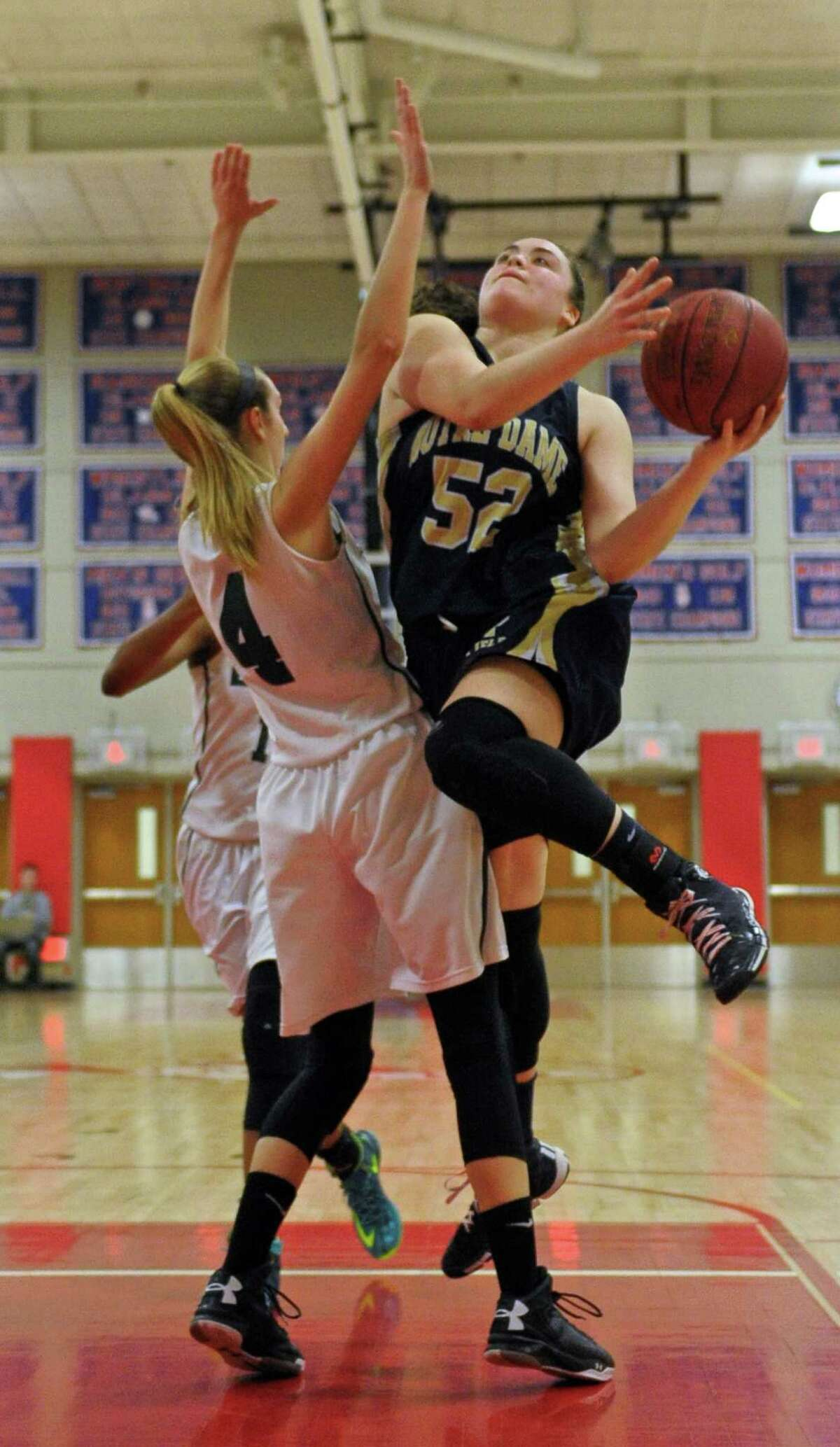 Notre Dame-Fairfield's Taylor Ceballos is fouled on her way to the basket by Enfield's Erica Lovering in Friday night's game. Ceballos had 20 points, 16 from the foul line.