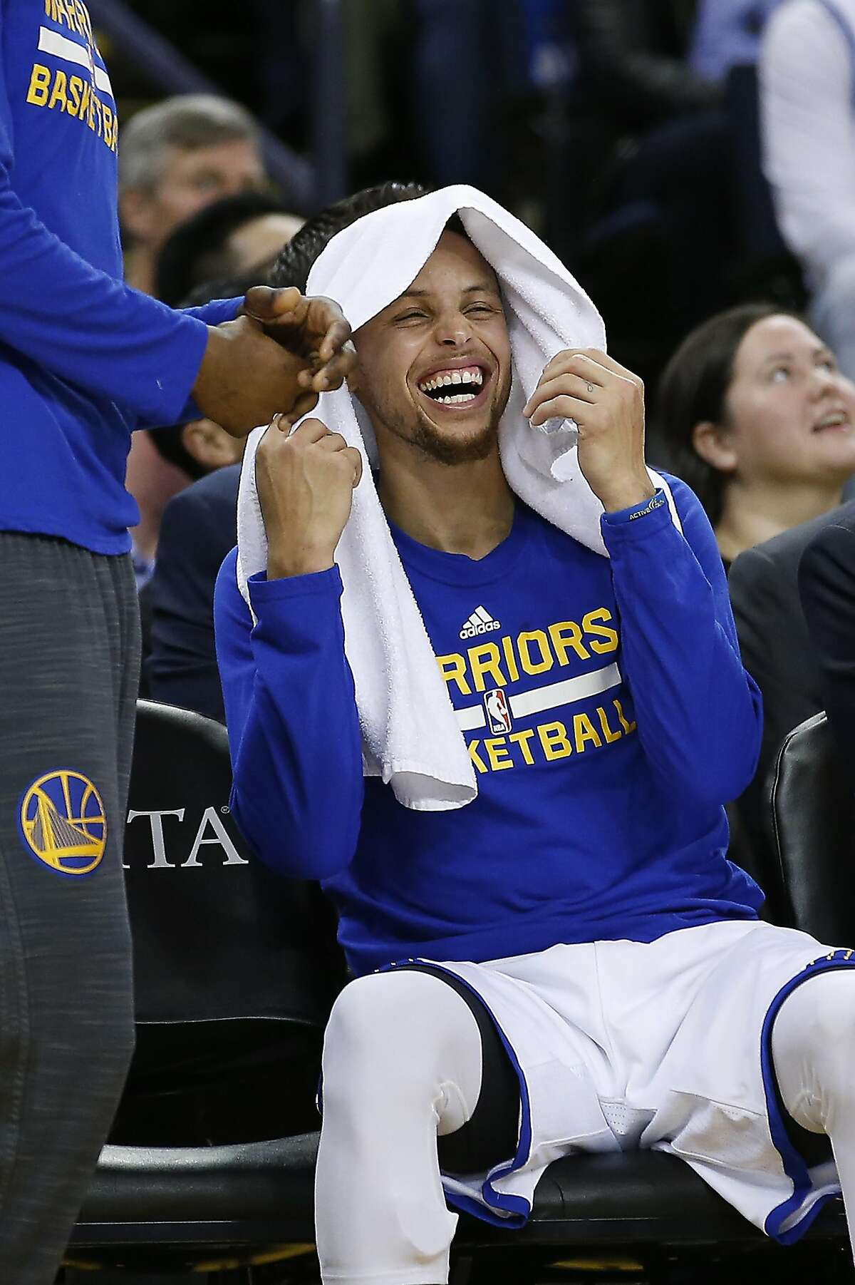 Golden State Warriors' Stephen Curry laughs on the bench during the first half against the Portland Trail Blazers in a NBA game at Oracle Arena in Oakland, Calif., on Friday, March 11, 2016.