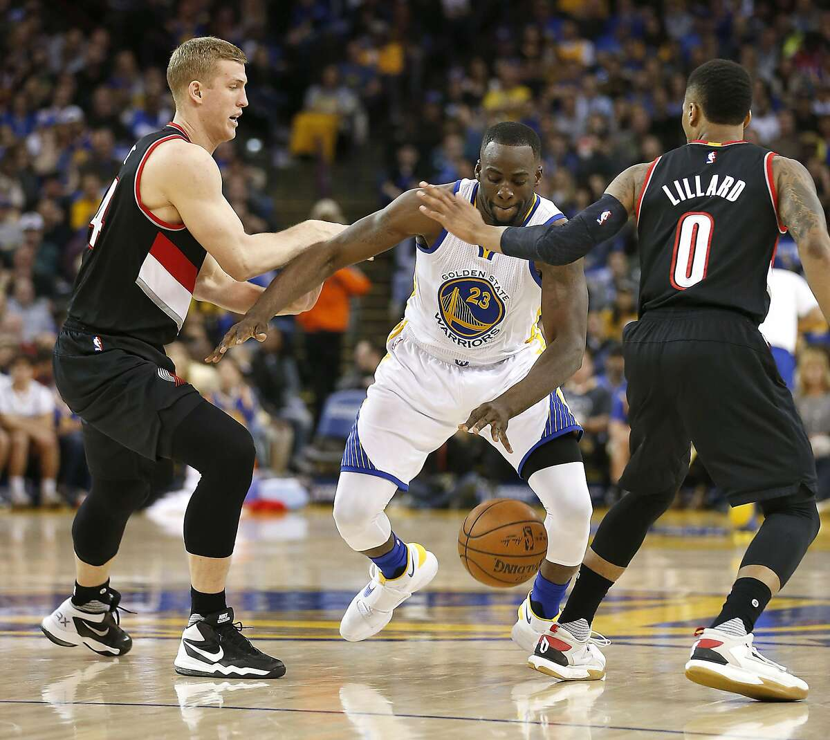 Golden State Warriors forward Draymond Green (23) drives the ball between Portland Trail Blazers' Mason Plumlee, left, and Damian Lillard (0) during the first half NBA game at Oracle Arena in Oakland, Calif., on Friday, March 11, 2016.
