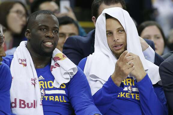 Golden State Warriors forward Draymond Green, left, and Stephen Curry, right, watch the game from the bench during the first half against Portland Trail Blazers NBA game at Oracle Arena in Oakland, Calif., on Friday, March 11, 2016.