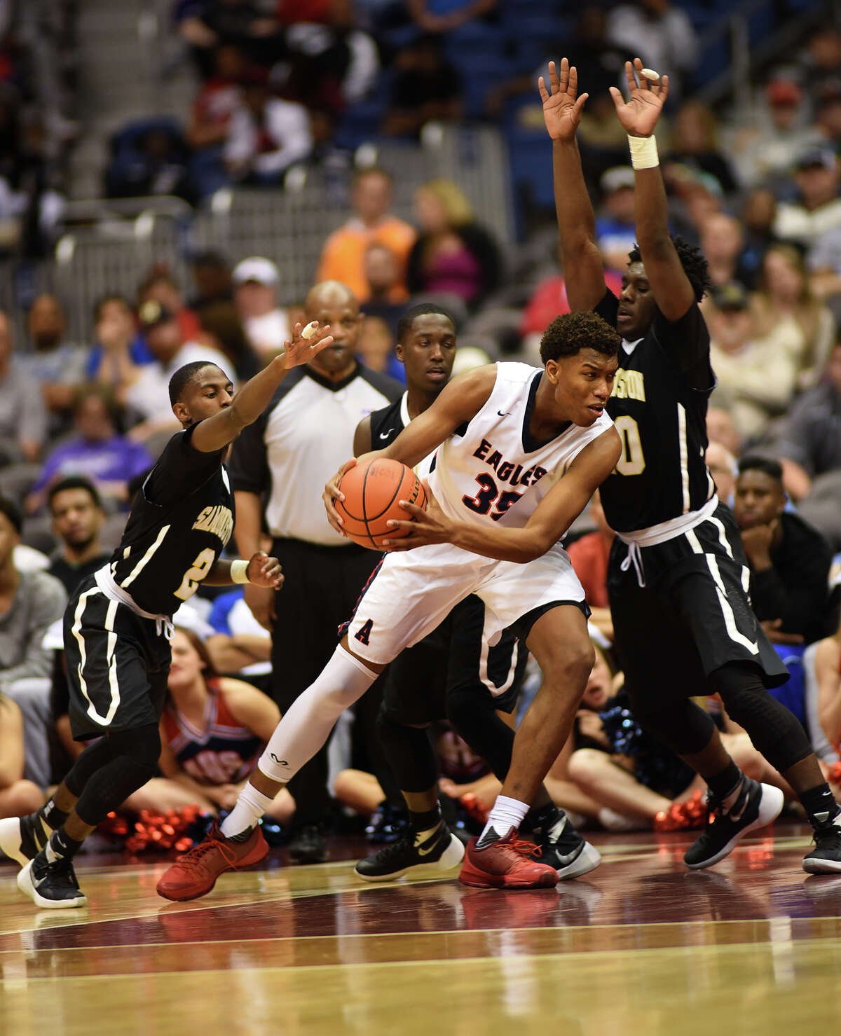 Atascocita junior forward Fabian White, center, drives to the hoop between Sam Houston defenders Lennard Robinson (2) and Terrell Wilson during fourth quarter action of their Class 6A boys basketball state semifinal matchup at the Alamodome in San Antonio on Friday, Mar. 11, 2016. (Photo by Jerry Baker/Freelance)