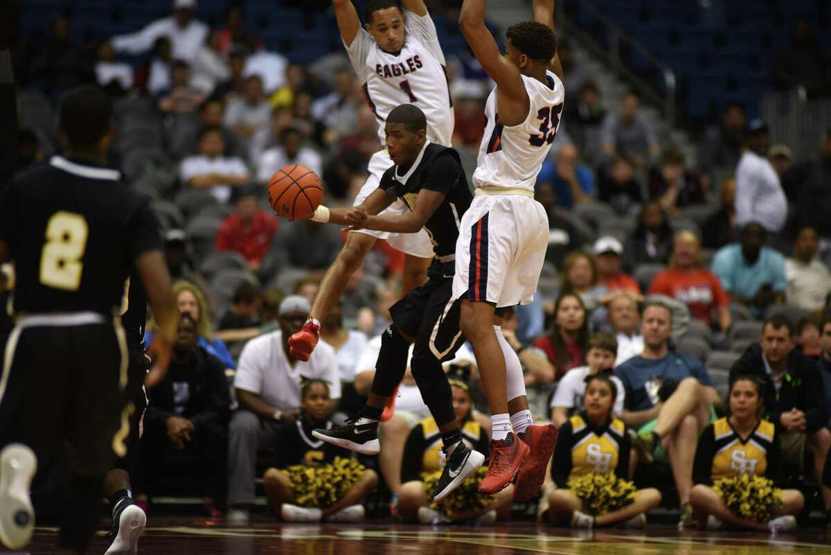 Sam Houston senior guard Lennard Robinson (2) works for a pass between Atascocita defenders Brandon Brooks-Loville (1) and Fabian White (35) during fourth quarter action of their Class 6A boys basketball state semifinal matchup at the Alamodome in San Antonio on Friday, Mar. 11, 2016. (Photo by Jerry Baker/Freelance)