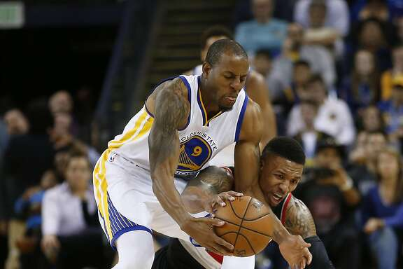 Golden State Warriors forward Andre Iguodala (9) battles for a loose ball against Portland Trail Blazers guard Damian Lillard (0) during the second half NBA game at Oracle Arena in Oakland, Calif., on Friday, March 11, 2016. Warriors won 128-112.