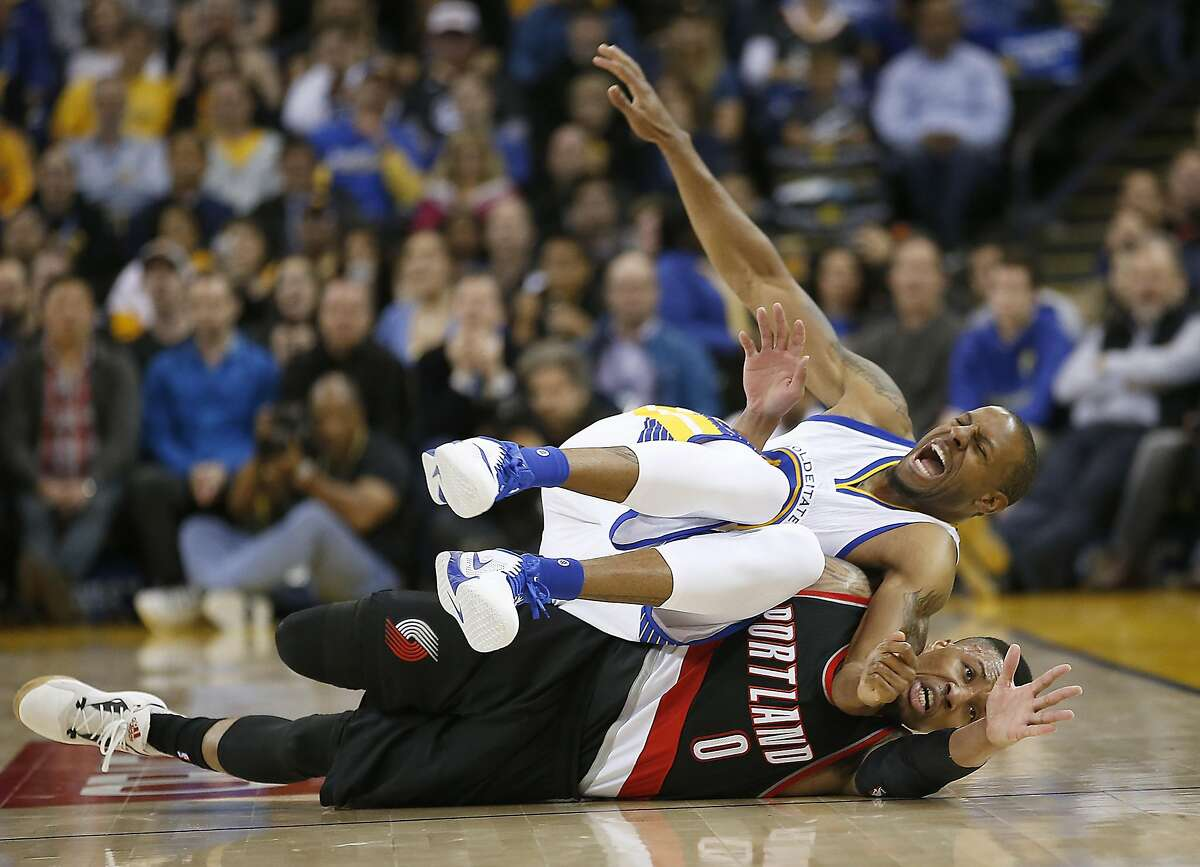 Golden State Warriors forward Andre Iguodala (9) grimmes after turning his ankle battling for a loose ball against Portland Trail Blazers guard Damian Lillard (0) during the second half NBA game at Oracle Arena in Oakland, Calif., on Friday, March 11, 2016. Warriors won 128-112.