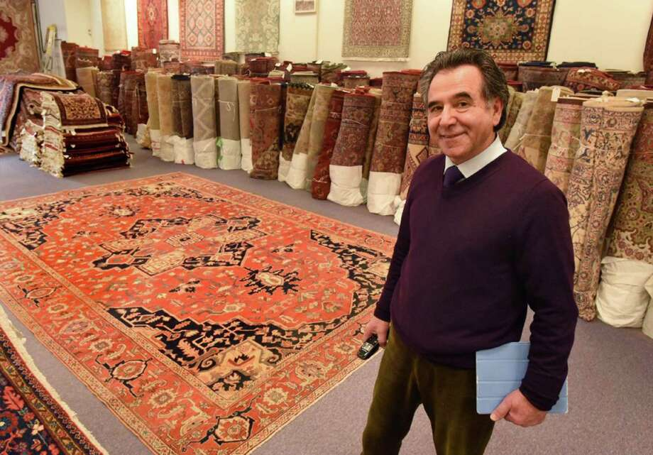 Esmail Borhani, owner of Borhani Rug Co. in suburban Baltimore, represents the fourth generation of his family in the business. On the floor behind him is a turn-of-the-century Serapi Persian rug, created using vegetable dyes. Photo: Amy Davis, MBR / Baltimore Sun