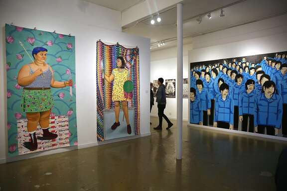 "Curator Ani Rivera talks about  the ""Womxn are Perfect!"" art at Gallery De La Raza in San Francisco, California,  on friday, march 11, 2016.  At left are two pieces of artwork from Mia Duran.  Far left is Codex#lookhowcuteiam, Francisca Mia, 2014, oil, acrylic, tissue paper, crepe paper, holographic paper, oil cloth, duct tape, upholstery fabric, and flower decals.  In the middle is Codex#lookhowcuteiam, Sara Fina, 2014, oil, acrylic, tissue paper, molding medium, holographic paper, oil cloth, gold thread on paper.    At far right is artwork from T.W. Five based in San Francisco."