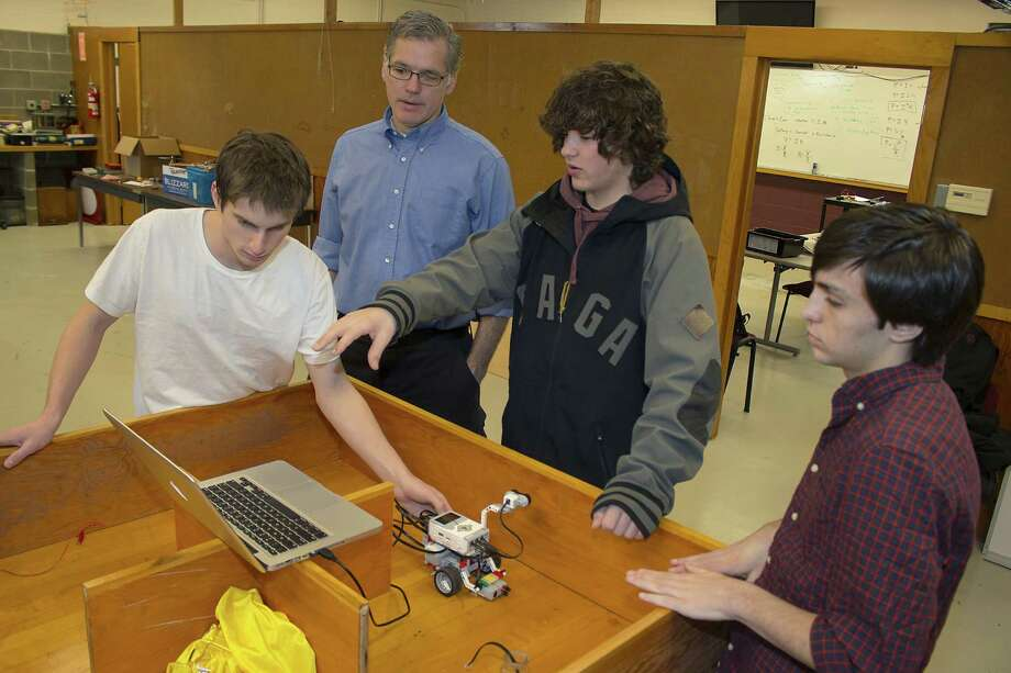 Darrow School in New Lebanon has launched its first elective in robotics for the spring semester. Students are working in teams to design, construct and operate fixed and mobile devices. Here, teacher and Science Department chair Jim Bennett, second from left, and seniors Liam Heeger of New York City, Jonathan Crowell of Chatham and Chris Earley of East Greenbush check the software programming on their rescue robot during class.  (Submitted photo)