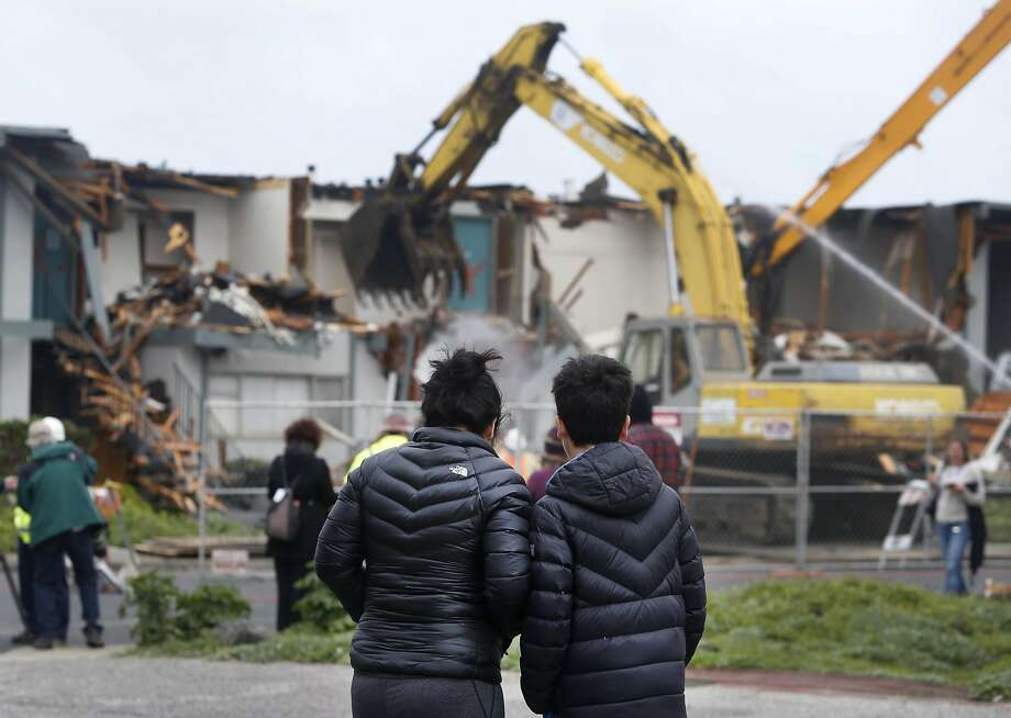 Neighbors Luciana Santa Rosa and her son Derick, 11, watch the demolition on Esplanade Avenue. Photo: Paul Chinn, The Chronicle