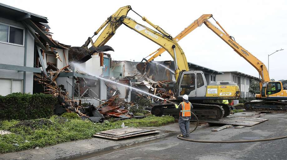 A demolition crew tears down an apartment building on Esplanade Avenue in Pacifica, Calif. on Saturday, March 12, 2016. The doomed building has been clinging on the precipice of a crumbling cliff since it was originally red-tagged in 2010. Photo: Paul Chinn, The Chronicle