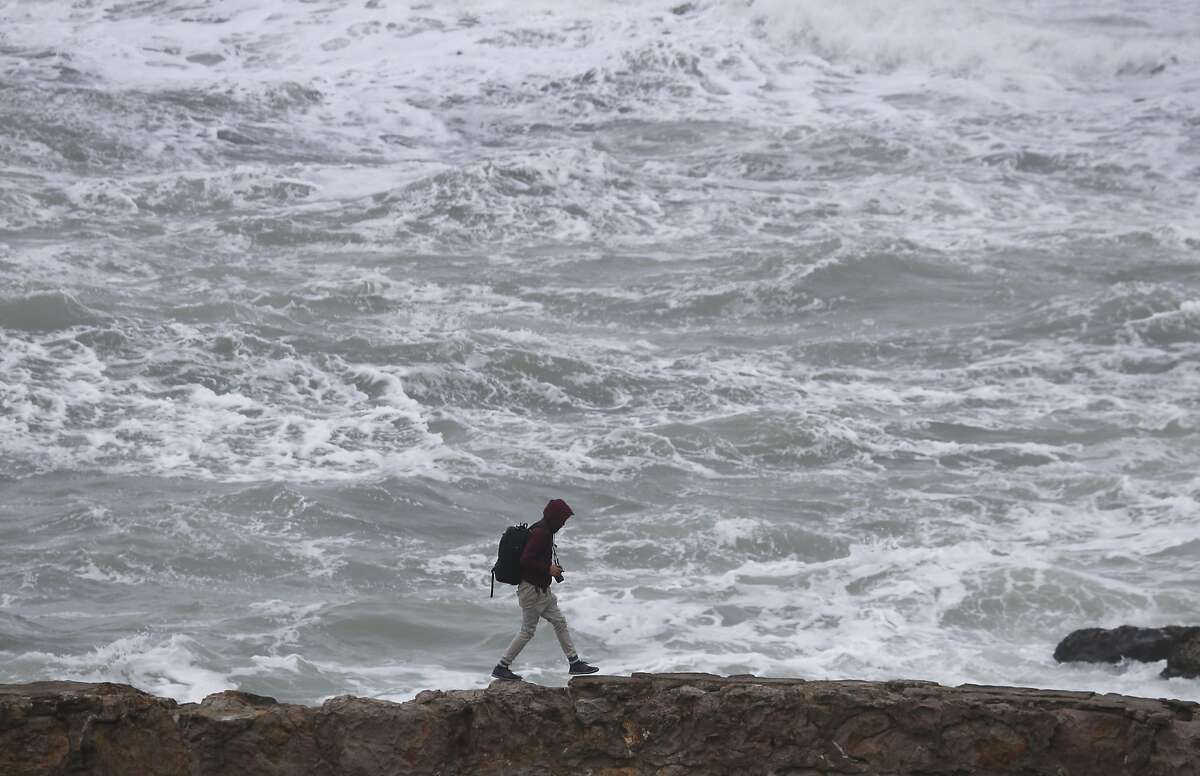 A man walks on a ledge of the old Sutro Baths in front of roiling surf in San Francisco. A study reports that 700,000 coastal residents in the Bay Area could be forced to move from their low-lying neighborhoods because of rising sea levels.
