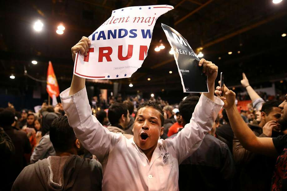 A protester shows off ripped Donald Trump campaign signs after it was announced the rally for the Republican presidential candidate was cancelled at the UIC Pavilion in Chicago on Friday, March 11, 2016. Photo: Chris Sweda, TNS