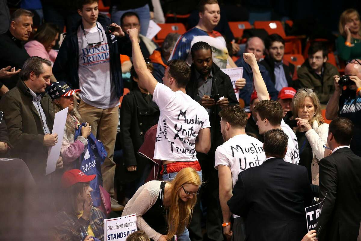 """Protestors wearing shirts reading """"Muslims United Against Trump"""" are escorted out the UIC Pavilion in Chicago prior to the start of a rally for Republican presidential candidate Donald Trump at the UIC Pavilion in Chicago on Friday, March 11, 2016. (Chris Sweda/Chicago Tribune/TNS)"""